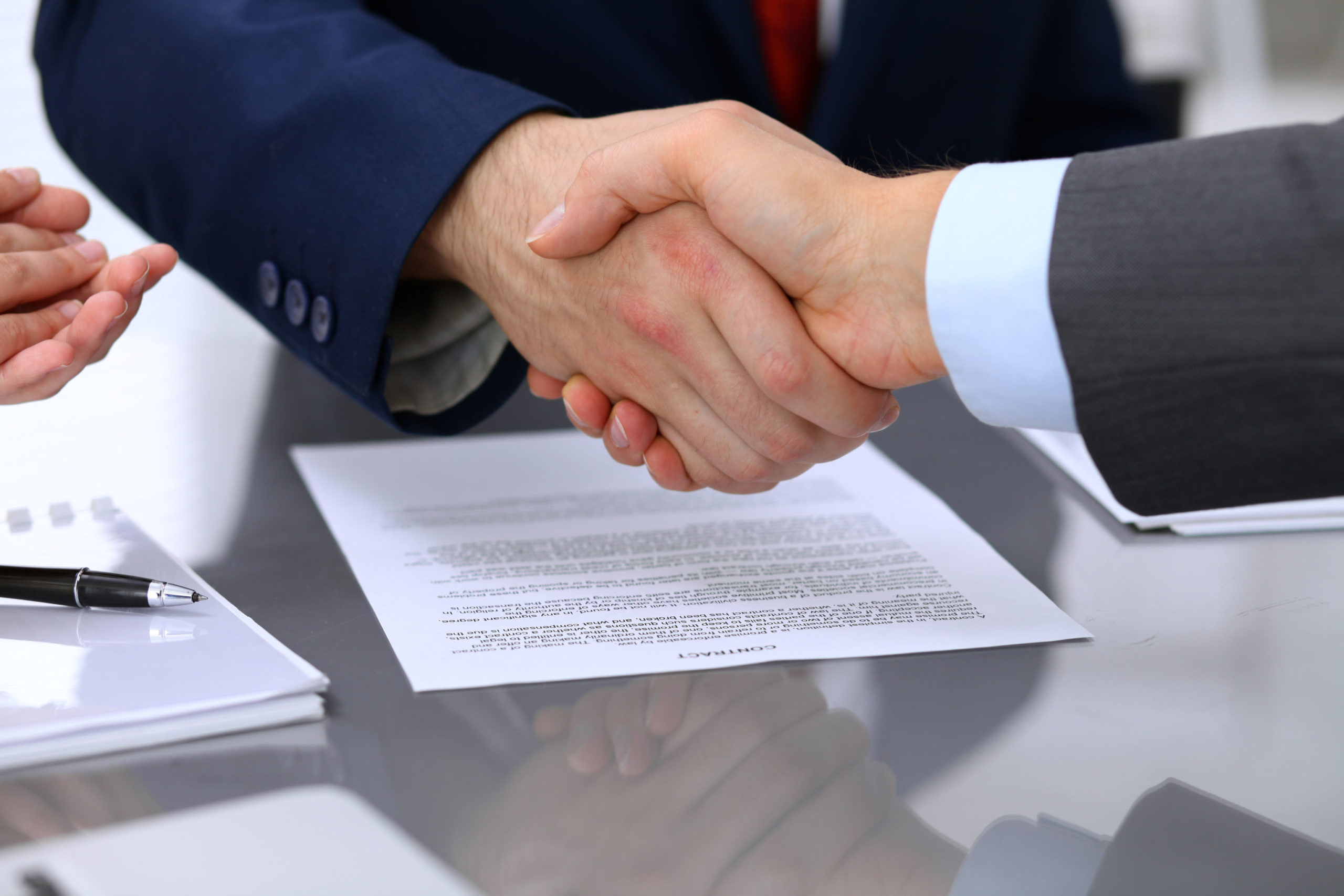 shaking hands and signing agreements